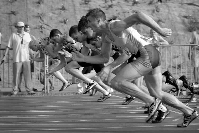 athletes running on track and field oval in grayscale photography